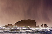 Rain is backlit by the setting sun as it falls on sea stacks surrounded by turbulent seas off the shore of Second Beach, Olympic National Park, Washington.