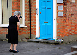 © Licensed to London News Pictures. 08/04/2013. London, UK A woman from the conservative office photographs flowers left on the doorstep of former Prime Minister Margaret Thatcher's constituency offices in Finchley, London, the day after she died from a stroke aged 87. Photo credit : Clare O Hagan/LNP