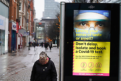 © Licensed to London News Pictures. 31/12/2020. Manchester , UK.  A woman walks past a Government coronavirus as she walks in central Manchester this morning.  The county of Greater Manchester from Thursday 31 December will move into Tier 4 following a spike in coronavirus cases. Photo credit:  Ioannis Alexopoulos/LNP
