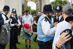 London, UK. 3 June, 2019. A man who wore a pro-Trump hat among protesters attending a noise demonstration outside Buckingham Palace against the state visit of President Trump to the UK is questioned by police officers. The US President is scheduled to attend a banquet at Buckingham Palace this evening.