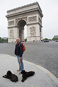 Man walking his two dogs near the Arc de Triomphe. The Arc de Triomphe de l'Etoile is one of the most famous monuments in Paris. It stands in the centre of the Place Charles de Gaulle.