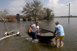 25 Sept, 2005.  Carlyss, Louisiana.  Hurricane Rita aftermath. <br /> Local cajun man Aaron Stokes and friend Chase Reider put in their boat to tour the swamps and bayou's checking on neighbours and their homes.<br /> Photo; ©Charlie Varley/varleypix.com