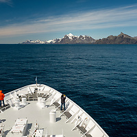 Guests on the bow of the National Geographic Orion look ahead to Elsehul, a bay on the northwest coast of South Georgia Island.