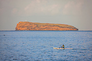 A man paddles in the Pacific Ocean toward the Hawaiian islet of Molokini. A humpback whale is visible on the left side of the frame, swimming between the man and the islet. Molokini is partially submerged volcanic crater located west of the island of Maui.
