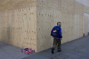 A man with a Union Jack rusksack walks past a matching discarded covered box left on the corner of construction hoarding plyboard in Trafalgar Square, London. With the backdrop of plyboard composite that acts as a construction screen on this busy pavement, the landscape is a juxtaposition of an incongruous feature in central London - a statement of coincidence and national quirkiness.
