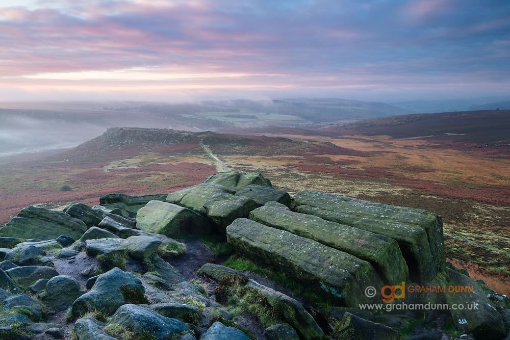 Gritstone blocks on Higger Tor's south-east corner, with Hathersage Moor and Carl Wark (Iron Age Hill Fort) in the distance. A classic dark peak scene captured during an autumn dawn. Peak District National Park, Derbyshire, England, UK. October.