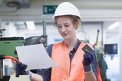 Young female engineer holding machine part with paper in an industrial plant, Freiburg im Breisgau, Baden-Wuerttemberg, Germany