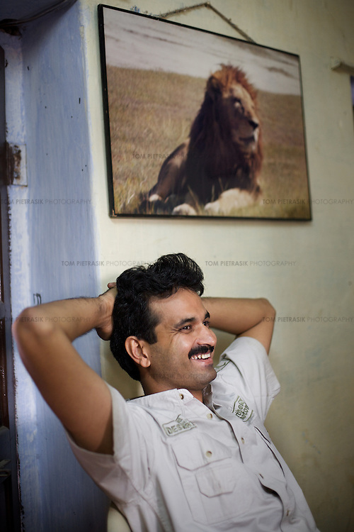 Dharmendra Khandal of Tiger Watch in the Khandar town office of range officer J.S. Kala on the edge of the Ranthambore national park. Kala is one of the few forest offials to have actively pushed for the prosecution of poachers. Many in the forest department find that the simple acknowledgment of poaching is considered by colleagues to be a slur on the forest department. ..Sariska National Park in Rajasthan was once home to dozens of tigers but by 2005 poaching had resulted in their complete eradication. Recognising the urgent need for intervention, the Indian and Rajasthan-state governments began the reintroduction of tigers into Sariska. Two cats were airlifted 200 km from Ranthambore National Park in June 2008. On November 5th an attempt to relocate a third tiger was postponed until later in the month. This relocation strategy is certainly an important part of the tiger conservation effort but many, including those like Dharmendra Khandal of the NGO Tiger Watch, argue that it will never be entirely successful without properly confronting the three essential issues that threaten tiger populations: poaching, habitat loss and the hunting of prey-base animals. In turn, these three issues cannot be addressed without acknowledging the malign influence of caste, poverty and poor administrative accountability. Poaching is almost exclusively undertaken by extremely poor and marginalised groups, including the Mogia caste who, without education, land and access to credit have limited alternative means of income. Many in the Mogia community also hunt bush meat for both their own consumption and to sell to others. This results in a depletion of the prey-base upon which tigers feed. Encroachment and grazing by those including the Gujar people who raise dairy herds, have led to habitat loss in Sariska and other parks. To properly tackle the problem of hunting and encroachment, the government must provide alternative livelihoods for marginalised groups and relocate them to viabl