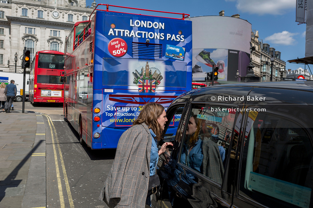 A lady speaks to a taxi driver in front of a London tour bus featuring an illustration of tourist attractions, with an iVenture card saves visitors up to 50% on tickets at the capital's landmarks, on 1st May, in Piccadilly Circus, London, England.