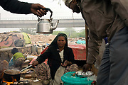 Sheela ('more than 60 years old') at her tea stall on waste ground near Nehru Place. Sheela came to Delhi in 1981 from Rajasthan with her husband and three children. Over the years they all died leaving her alone. New Delhi, India