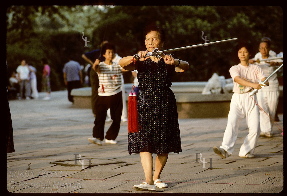 An older woman practices sword play with her class at sunrise in Jin An Park; central Shanghai China