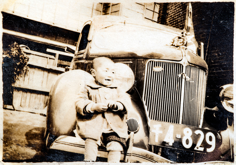 little child sitting on the fender of a car Japan ca 1930s