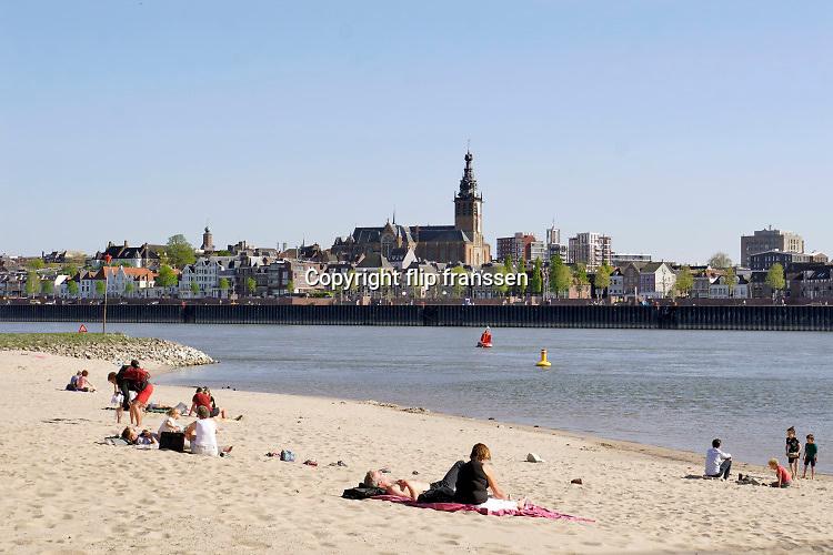 Nederland, Nijmegen, 22-4-2020  Langs de Waal liggen alweer mensen in de zon, genietend van een mooie lentedag met warm weer . Aan de overkant ligt de oude stad, benedenstad, met de stevenskerk op een heuvel . Vanwege de coronamaatregelen liggen de mensen minstens anderhalve meter uit elkaar . Foto: Flip Franssen