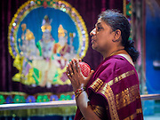 07 JANUARY 2014 - SINGAPORE:   A woman prays after afternoon pooja in Sri Veeramakaliamman Temple, a Hindu temple located in Little India in the southern part of Singapore. The Sri Veeramakaliamman Temple is dedicated to the Hindu goddess Kali, fierce embodiment of Shakti and the god Shiva's wife, Parvati. Kali has always been popular in Bengal, the birthplace of the labourers who built this temple in 1881. Images of Kali within the temple show her wearing a garland of skulls and ripping out the insides of her victims, and Kali sharing more peaceful family moments with her sons Ganesha and Murugan. The building is constructed in the style of South Indian Tamil temples common in Tamil Nadu as opposed to the style of Northeastern Indian Kali temples in Bengal. PHOTO BY JACK KURTZ