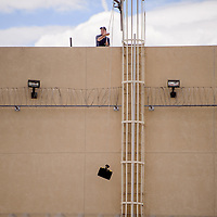 072315       Cable Hoover<br /> <br /> One responder hauls equipment to the roof during a disturbance at the McKinley County Detention Center Thursday.