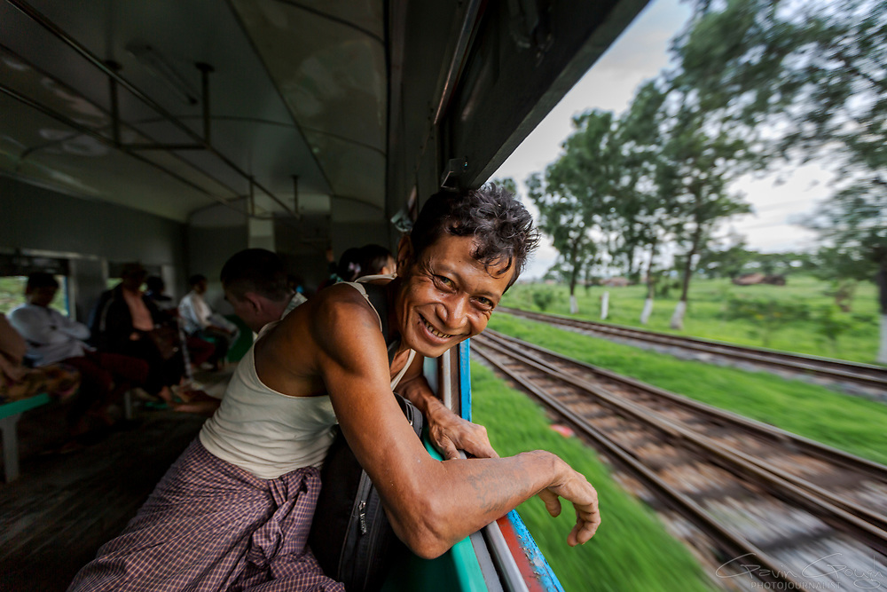 """A passenger leaning out of a window of the """"Circular Railway"""" in Yangkok, Myanmar."""