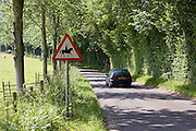 Car passes Accompanied horses or ponies warning sign by side of road, Dorset, UK