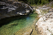 Cooling waters of the Bosso River in Secchiano, Umbria, Italy. Here the crystal clear waters carve their way through the rocks.