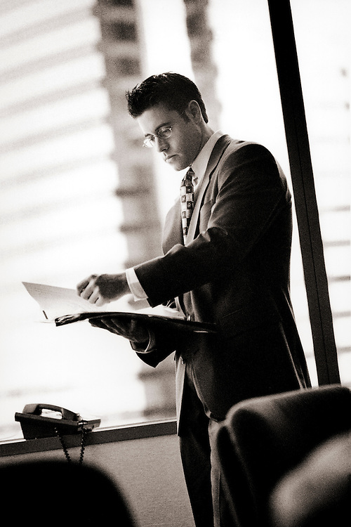 Businessman looking at papers in office (B&W)