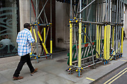 Seen from the rear, a man wearing a chequed shirt walks beneath scaffolding in a sidestreet, on 29th April 2019, in London, England.
