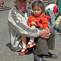 South America, Ecuador, Quito. Ecuadorian man and his granddaughter enjoy Quito's public plaza.