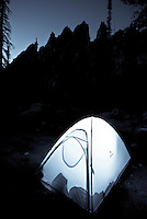 A tent glows below the Verita Ridge spires in the Sawtooth Mountains, Idaho.