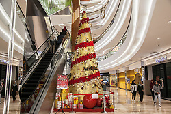 December 18, 2018 - Medan, North Sumatra, Indonesia - Indonesian Muslim women walk beside a Christmas tree ornament in a shopping center in Medan, North Sumatra on December 17, 2018. The world's most populous Muslim country is preparing to celebrate the Christmas holiday and new year's eve, where the and shopping malls in Indonesia filled with garnish of Christmas decorations. (Credit Image: © Albert Ivan Damanik/ZUMA Wire)
