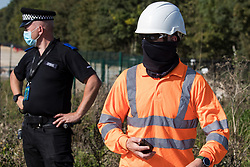 West Hyde, UK. 14th September, 2020. A HS2 worker makes a statement regarding the ownership of property directly in front of him to environmental activists from HS2 Rebellion using lock-on arm tubes to block a gate to the South Portal site for the HS2 high-speed rail link. Anti-HS2 activists blocked two gates to the same works site for the controversial £106bn rail link, one remaining closed for over six hours and another for over nineteen hours.