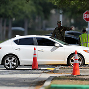 Army National Guard members direct residents who are aged 65 and over who are concerned they may have acquired Coronavirus (COVID-19) at the Orange County Convention Center on Friday, March 27, 2020 in Orlando, Florida. (Alex Menendez via AP)