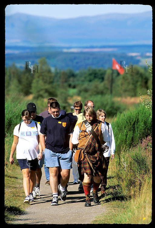 Tourists follow guide dressed as Highlander along Jacobite battle line, flagged in red, at Culloden Moor; Inverness, Scotland.