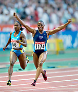 Kelli White of the United States celebrates after winning the 100 meters in 10.85 seconds in the IAAF World Championships in Athletics at Stade de France on Sunday, Aug, 24, 2003.