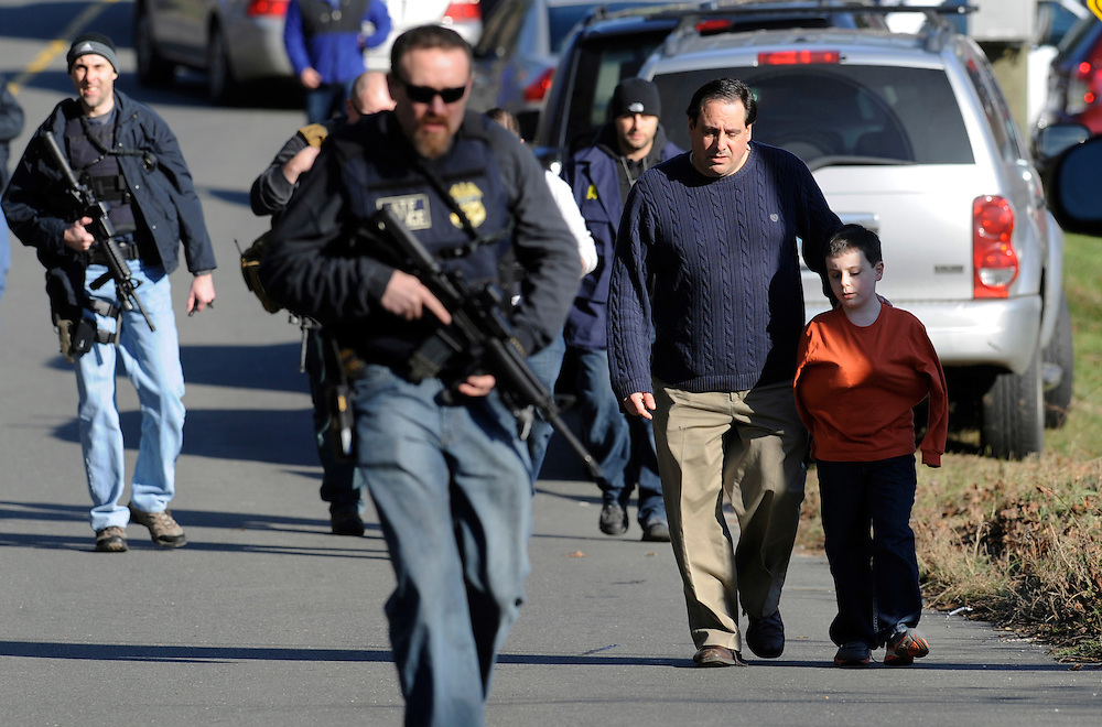 A man and boy walk with armed police after being reunited at a staging area. (AP Photo/Jessica Hill)