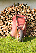 Old red metal wheelbarrow leaning against pile wood logs in garden, Cherhill, Wiltshire, England, UK