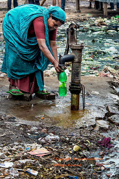 Clean Water: A lady risks the garbage and filth to use a manual water pump and fill a container with water, Mymensingh Bangladesh.