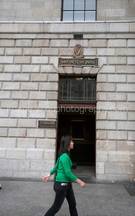 Woman walking past the door of The General Post Office (GPO) in Dublin, the headquarters of the Irish postal service An Post and Dublin's main post office. Located in the centre of the city on O'Connell Street, it is one of Ireland's most famous buildings and was the last of the great Georgian public buildings to be erected in the capital. During the Easter Rising of 1916, the GPO served as the headquarters of the uprising's leaders.