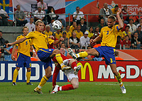 Photo: Glyn Thomas.<br /> Sweden v England. FIFA World Cup 2006. 20/06/2006.<br /> <br /> England's Wayne Rooney (C) gets caught between Sweden's Olof Mellberg (R) and Niclas Alexandersson.
