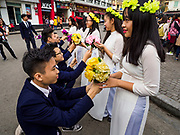 "24 DECEMBER 2017 - HANOI, VIETNAM: Students pretend to stage a group proposal in the old quarter of Hanoi. The old quarter is the heart of Hanoi, with narrow streets and lots of small shops but it's being ""gentrified"" because of tourism and some of the shops are being turned into hotels and cafes for tourists and wealthy Vietnamese.           PHOTO BY JACK KURTZ"