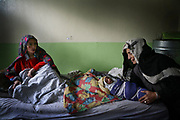 Qamar, left, a 26-year-old tuberculosis patient from Shohada district, sits in her hospital bed with her newborn son and mother-in-law, Khalisa, inside the recovery room at Faizabad Provincial Hospital, Faizabad in Badakshan province, Afghanistan, Friday, May 11, 2007.