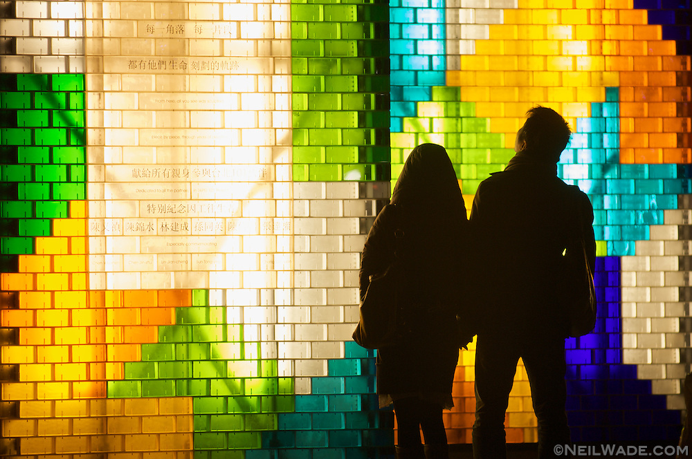 A couple looks at a display of colorful blocks located at the base of Taipei 101 in Taipei, Taiwan.