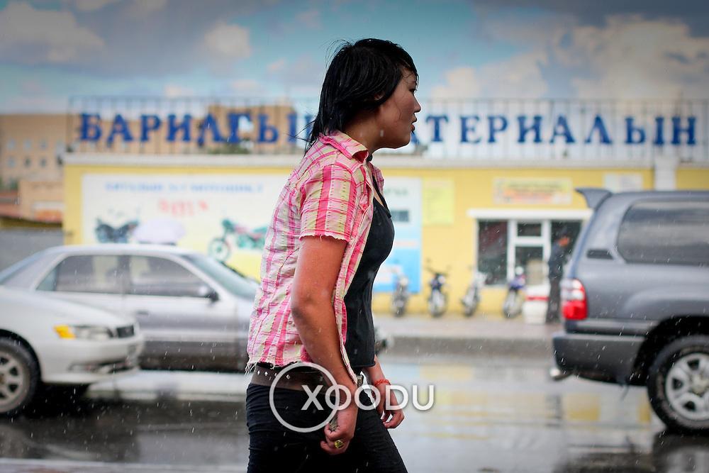 Young wet girl walks along city street in rain (Ulaanbaatar (Ulan Bator), Mongolia - Aug. 2008) (Image ID: 080831-1128461a)