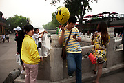 Standing on Yinding bridge holding a yellow smiley face balloon. Shichahai dates back to the Jin Dynasty. Around the lake there are ten famous Taoist and Buddhist temples and several formal royal mansions and gardens. The borders of the lakes are surrounded by large trees making Shichahai a famous scenic spot. In the summer tourists can rent boats to peddle on the lakes. In 1992 the municipal government of Beijing declared the district a Historical and Cultural Scenic District.