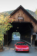 Red sports convertible driving through Woodstock Middle Bridge, a covered bridge in Vermont, New England, USA