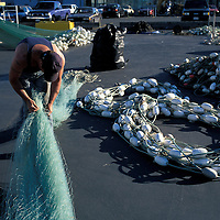 USA, Washington, Seattle, (MR) John Gaines works on salmon gillnet at Fisherman's Terminal on autumn afternoon
