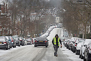 A workman crosses an icy minor road in the south London borough of Herne Hill, Lambeth during the bad weather covering every part of the UK and known as the 'Beast from the East' because Siberian winds and very low temperatures have blown across western Europe from Russia, on 1st March 2018, in Lambeth, London, England.