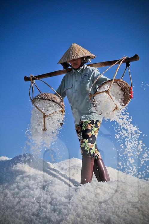 Worker dumps salt from her yoke in Doc Let salines, Khanh Hoa Province, Vietnam, Southeast Asia