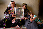 Ayseh, left, and Hana Dbabseh, center, hold the picture of their late husband, Issa Dbabseh. He was killed by Israeli soldiers after he had killed a Jewish settler two years ago, when Hana's last daughter, Wafa, right, was only 13 days old. After his death, the two wives became co-dependent on each other, sharing housework and brining up children together.