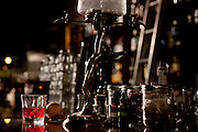 Sazerac with Absinthe Fountain.  Beverage specialties created by the talented bartenders and at Peche Restaurant and Bar, the first Absinthe bar in Austin. Located in the Warehouse District. Hoouse made tinctures in small brown bottles with droppers, and other cocktail essentials are on the bar. A Sazerac with a lemon twist sits on the bar. This cocktail originated in New Orleans in 1838 by Antoine Amedie Peychaud, and became the first branded cocktail.
