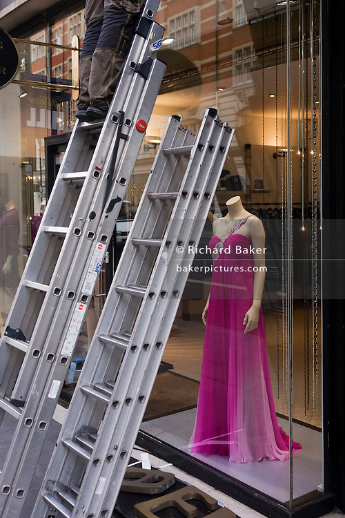 A headless mannequin juxtaposes with the lower legs of a workman up a set of ladders in London's Knightsbridge.