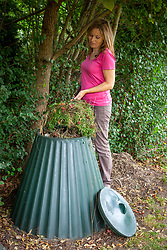 Adding suitable material to a compost bin in autumn