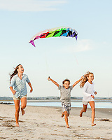 Three siblings, two sisters and their brother, run down the beach with a colorful kite in the sky above them.